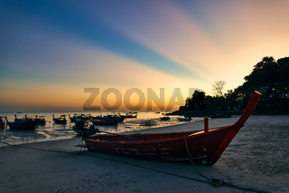 Fantastic sunset with sun light rays on tropical island and boats on beach