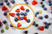 Wooden bowl full of yoghurt with strawberries and blueberries