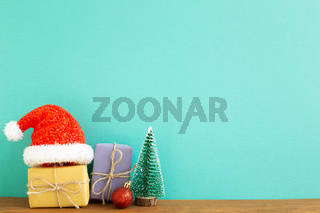 Christmas concept. Gift boxes with fir tree, bauble, santa claus hat on wooden table with green background