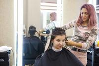 Female hairdresser cutting hair of cheerful woman