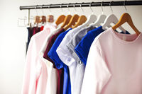 Colorful clothes hanging on rack in room