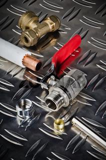 Plumbing inlet pipe valve on a metal surface