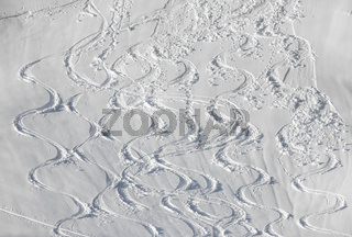 Wavy Ski tracks in deep snow on snowy mountain slope. White Winter sport background.