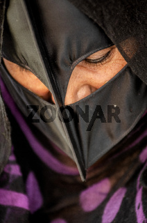 An Omani Bedouin woman wearing a traditional Batoola face covering, Oman