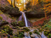 Waterfall in autumn with orange and yellow colors. Running clear, cold water in a forrest during autumn.