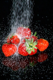 Pouring sugar on fresh red strawberries