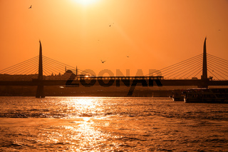 Golden Horn Bridge with the Yavuz Selim Mosque on the background at sunset. Istanbul. Turkey