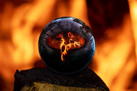 Campfire in a stone surround hearth reflected in a glass ball with orange background