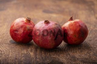 drei Granatäpfel auf dunklem Holz
