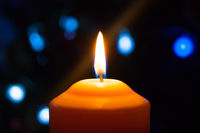 A burning orange candle on a dark background with blue lights - a Christmas New Year's eve divination mystic esoteric romance love mood. Horizontal photo, side, focus or defocus