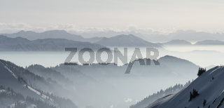 Snow Mountains Panorama in low lying inversion valley fog. Silhouettes of foggy Mountains. Scenic snowy winter landscape. View from Stuiben Swiss Alps, Allgau, Bavaria, Germany.