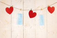 Red hearts and surgical face masks hanging on cord on white wooden background.