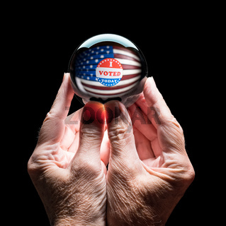 Hands holding a crystal glass forecasting ball to predict the result of the election