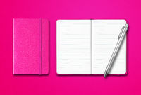 Pink closed and open notebooks with a pen isolated on colorful background