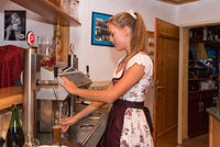 young waitress in dirndl pours at the hotel bar