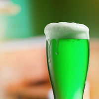 Glass of light green beer with thick foam.