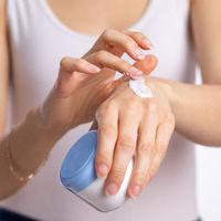 Woman applying hand cream to moisturize skin - stock photo