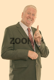 Studio shot of happy mature businessman smiling while pointing finger up