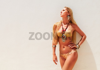 Sexy blond fashionable woman posing in a golden bikini