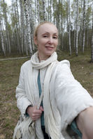 woman in a white jacket in a birch forest smiles for a selfie