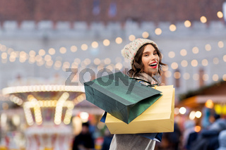 happy woman with shopping bags at christmas market