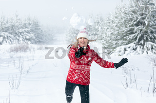 Snowball flying through the air as it leaves womans hands