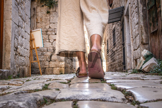 Detail shot of female legs wearing comfortable travel sandals walking on old medieval cobblestones street dring sightseeing city tour. Travel, tourism and adventure concept