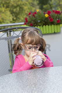 Girl sitting on patio and drinking a milkshake