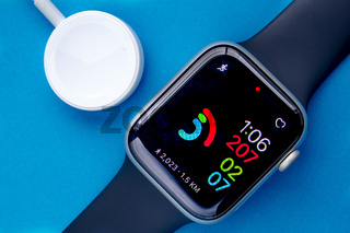 Calgary, Alberta, Canada. Nov. 19, 2020. An Apple Watch Series 6 with the Activity digital and a charger on a blue background.