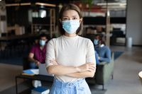 Portrait of asian businesswoman wearing face mask in creative office