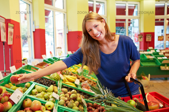 Frau greift nach Obst im Supermarkt