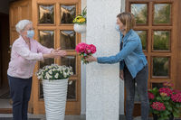 Senior woman with face mask gets flowers from neighbor woman with face mask