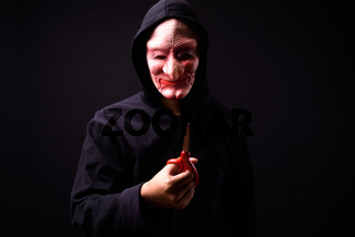 Portrait of young man with hoodie and horror mask holding scissors