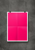 Pink folded poster hanging on a concrete wall with clips