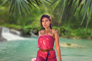 Young woman relaxing in lake water with tropical forest and waterfall behind her at luxury resort in Asia