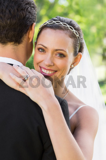 Happy bride embracing groom in garden