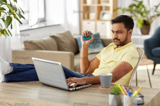 man with laptop and hand expander at home office