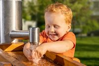 Little boy happily playing with tap water in a sunny playground