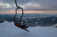 Alpine resortr ski lift with seats going over the sunset mountain skiing  slopes in extremally windy weather