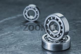 Three spherical roller bearings on slate near