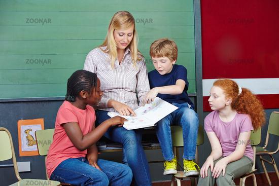 Lehrer im Unterricht mit Schulbuch
