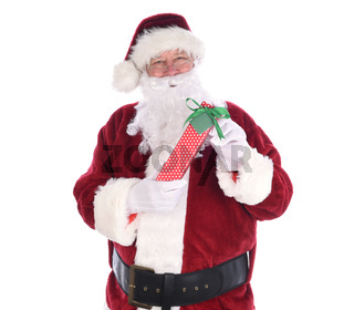 Santa holidng a polka dot paper wrapped Christmas Present, isolated on white.