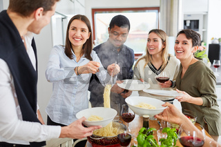 Freunde beim Spaghetti servieren für gemeinsame Mahlzeit