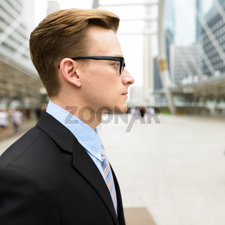 Profile view of young handsome blond businessman with eyeglasses in the city outdoors