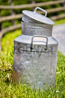 Eine Milchkanne aus Metall steht am Wegesrand