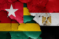 flags of Togo and Egypt painted on cracked wall