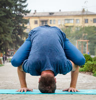 young man in yoga pose on the rug on the sidewalk against the backdrop of the city street