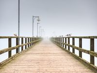 City wooden ocean pier for tourist against  misyt sky. Travel destination