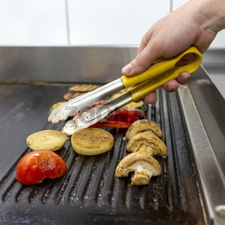 Cooking vegetables grill on the frying surface in black