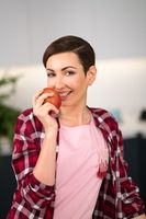 Smelling fresh apple holding it in a hand with a sexy eye contact on camera charming housewife wearing plaid shirt with a short hairstyle while cooking apple pie standing at the kitchen